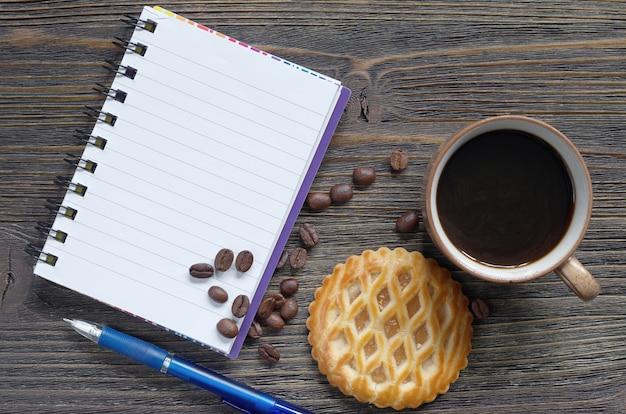 Notitieboekje, koffie en gebak met appelvulling