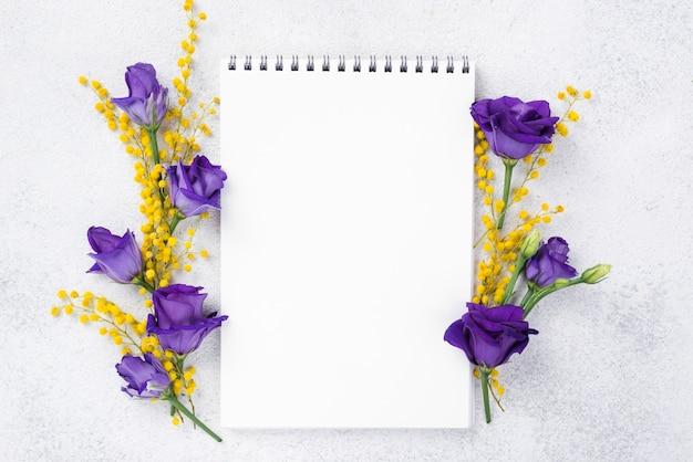 Notitieboekje met bloeiende bloemen naast