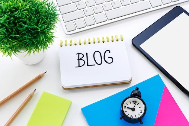 Notitieboekje met blogwoord op computerbureau