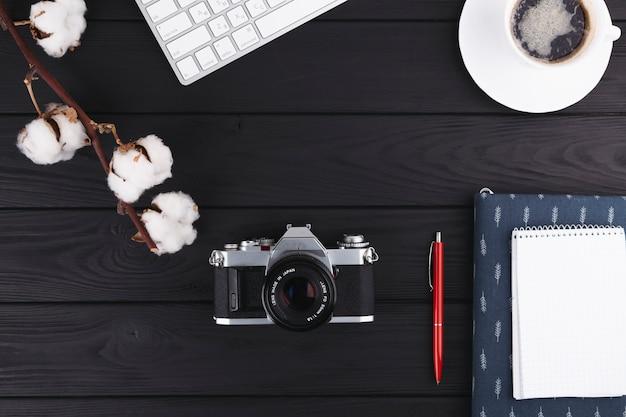 Notitieboekje met camera en koffie op lijst