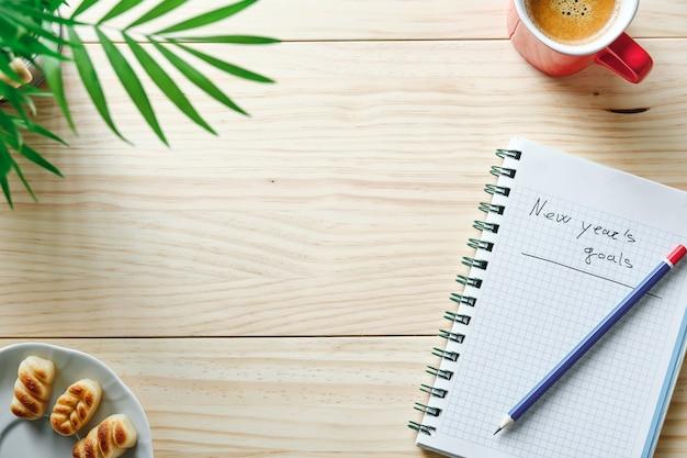 Notitieboekje met de woorden nieuwjaarsdoelen geschreven op een natuurlijke houten achtergrond met een blauw en rood potlood erop, wat groene bladeren ernaast en een kopje koffie in de hoek