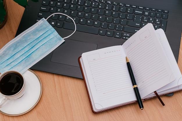 Notitieboekje met een pen, laptop, witte kop koffie en beschermend masker