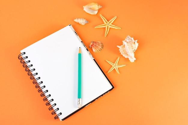 Notitieboekje met een potlood en zeeschelpen op sinaasappel en blauw