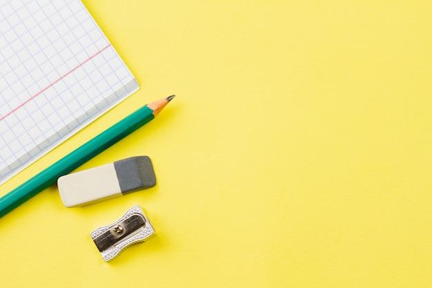 Notitieboekje met een potlood op een gele achtergrond.