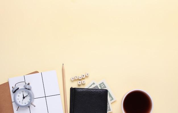 Notitieboekje met een potlood, portemonnee, wekker, kopje koffie op een beige achtergrond met het woord opstarten van houten letters.