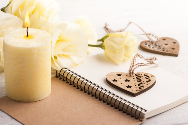 Notitieboekje met gele lisianthusbloemen en kaars