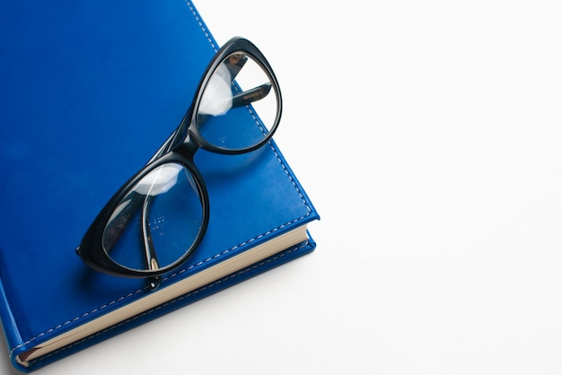 Notitieboekje met glazen en pen, boek met glazen, blauw notitieboekje met glazen, boek met kop thee
