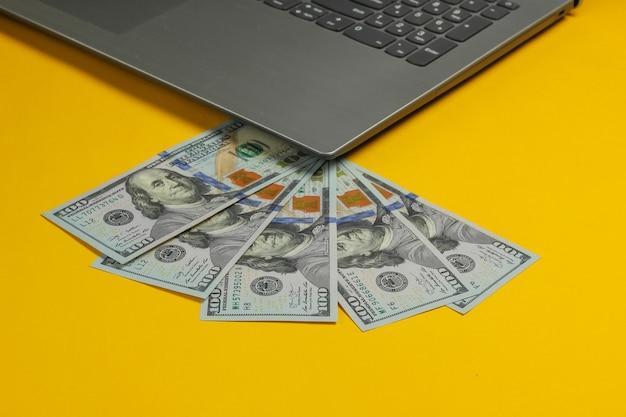 Notitieboekje met honderd dollarbiljetten op een gele achtergrond. online inkomsten, werken op afstand