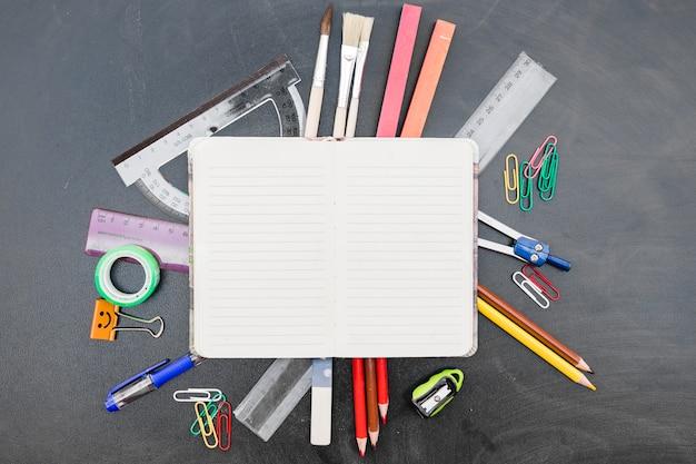 Notitieboekje met kantoorbehoeften op bord