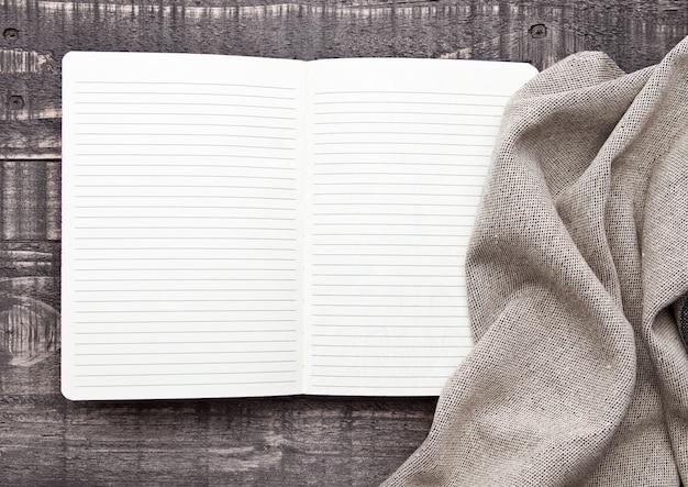 Notitieboekje met keukendoek op houten oppervlakte