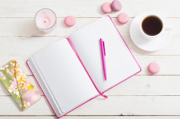 Notitieboekje met kopje koffie op witte houten tafel