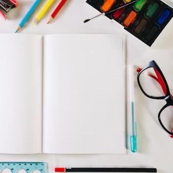 Notitieboekje met lege pagina's dichtbij kantoorbehoeften