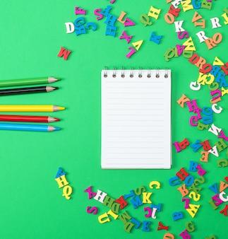 Notitieboekje met lege witte bladen en multicolored houten potloden