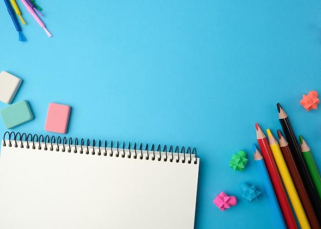 Notitieboekje met lege witte lakens, veelkleurige houten potloden, bovenaanzicht, concept van terug naar school, plat leggen