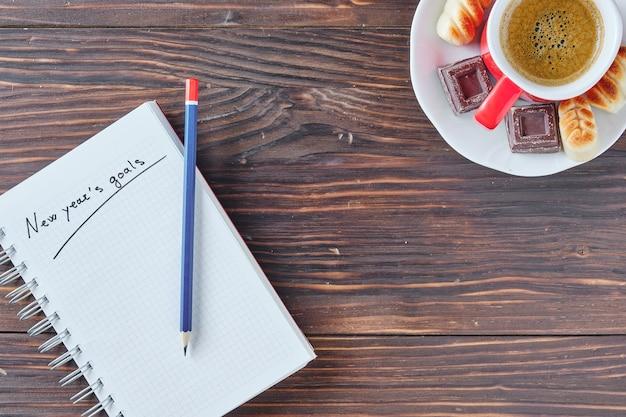 Notitieboekje met nieuwjaarsdoelen geschreven op een rustieke bruine houten achtergrond met potlood erop en rode kop koffie in de rechterbovenhoek met chocolade en marsepein aan de zijkant