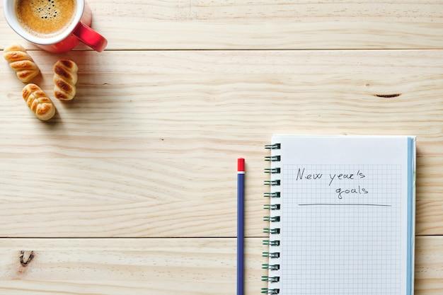 Notitieboekje met nieuwjaarsdoelen geschreven op houten achtergrond met potlood ernaast en rode kop koffie in de linkerbovenhoek