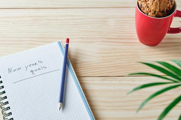 Notitieboekje met nieuwjaarsdoelen geschreven op houten achtergrond met potlood op groene bladeren aan de ene kant en rode kop in de linkerbovenhoek met koekjes erin