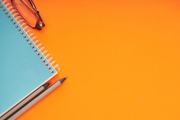 Notitieboekje met oogglazen en potloden op oranje achtergrond