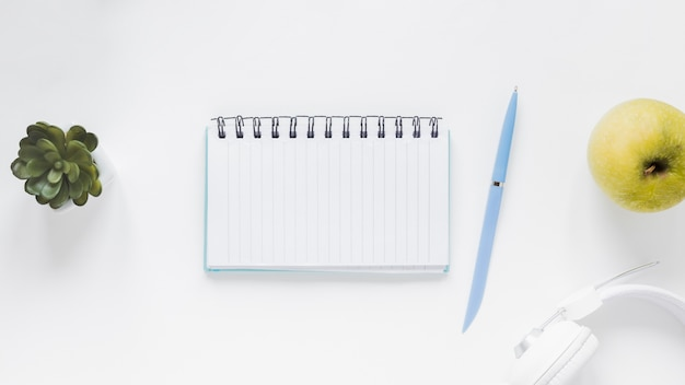 Notitieboekje met pen dichtbij appel en hoofdtelefoons op wit bureau
