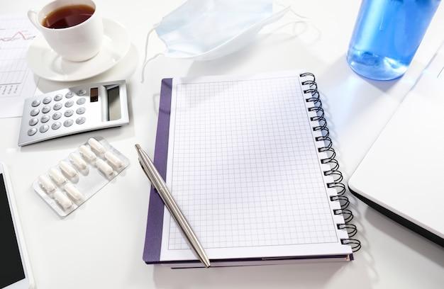 Notitieboekje met pen en beschermend masker op een witte lijst. zakelijke items en medische masker op een witte tafel.