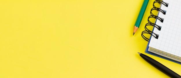 Notitieboekje met pen en potlood op een gele achtergrond.