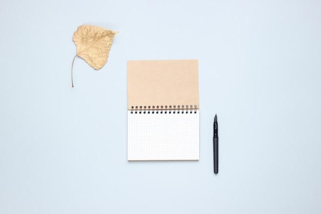 Notitieboekje met pen, gevallen herfstbladeren op een grijze tafel. herfstinspiratie, schrijven. bovenaanzicht, minimalisme. plat liggen