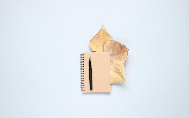 Notitieboekje met pen, gevallen herfstbladeren op een grijze tafel. herfstinspiratie, schrijven. bovenaanzicht, minimalisme