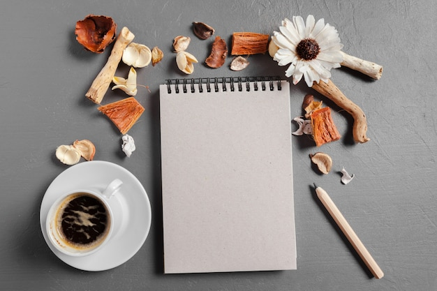 Notitieboekje met pen, koffie en bloem op tafel
