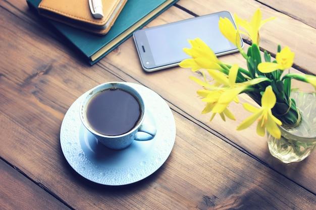 Notitieboekje met pen, koffie, telefoon en bloem op een houten tafel