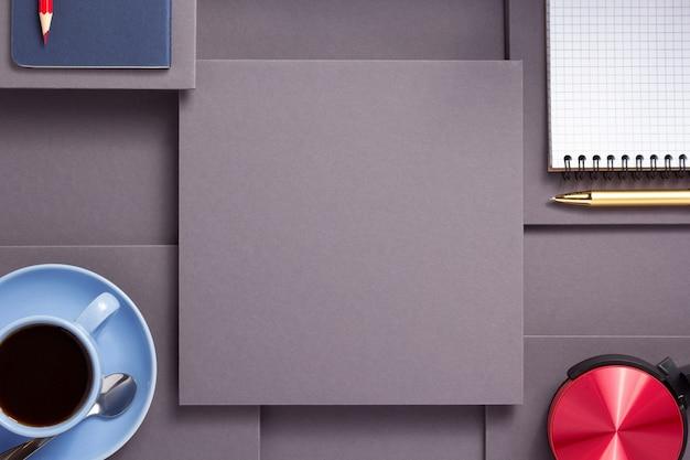 Notitieboekje met pen, koptelefoon en kopje koffie op abstracte grijze papieren achtergrond, minimalisme conceptstijl