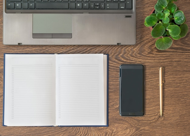 Notitieboekje met pen, notitieboekje en bloem op een houten lijst.