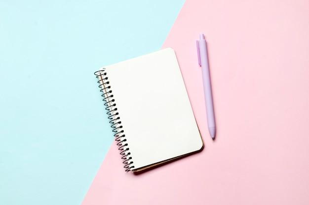 Notitieboekje met pen op een blauwe en roze achtergrond. plaats voor tekst