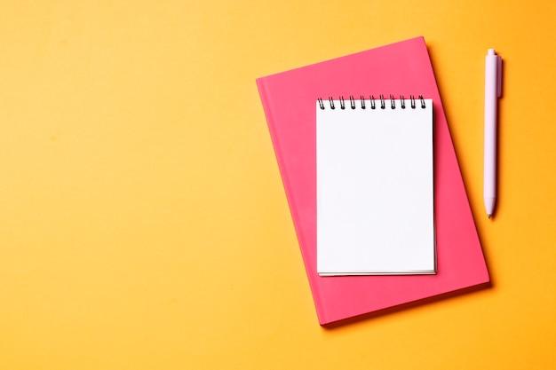 Notitieboekje met pen op een oranje achtergrond.
