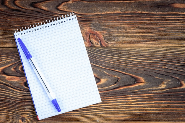 Notitieboekje met pen op houten bord