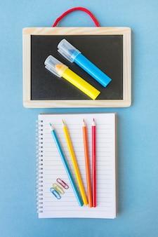 Notitieboekje met potloden dichtbij bord met tellers