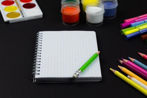 Notitieboekje met potloden en verf op zwarte achtergrond