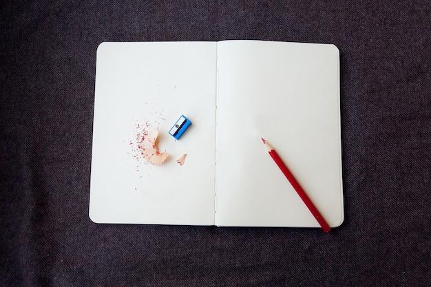 Notitieboekje met potlood en potloodkrullen op een bruine doekachtergrond