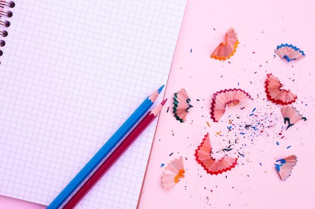 Notitieboekje met potlood en scherpte op roze achtergrond