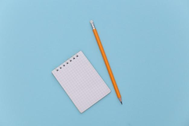 Notitieboekje met potlood op blauwe pastelachtergrond. bovenaanzicht