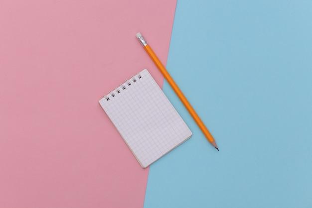 Notitieboekje met potlood op een blauw-roze pastelachtergrond. bovenaanzicht