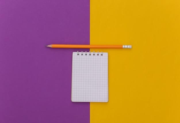 Notitieboekje met potlood op paars gele achtergrond. bovenaanzicht