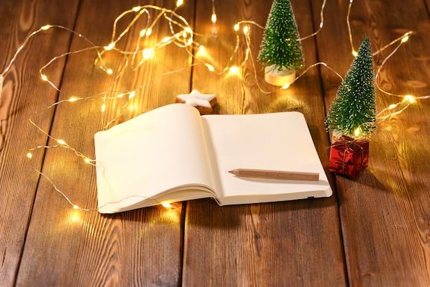 Notitieboekje met ruimte voor tekst over het kerstthema op houten tafel