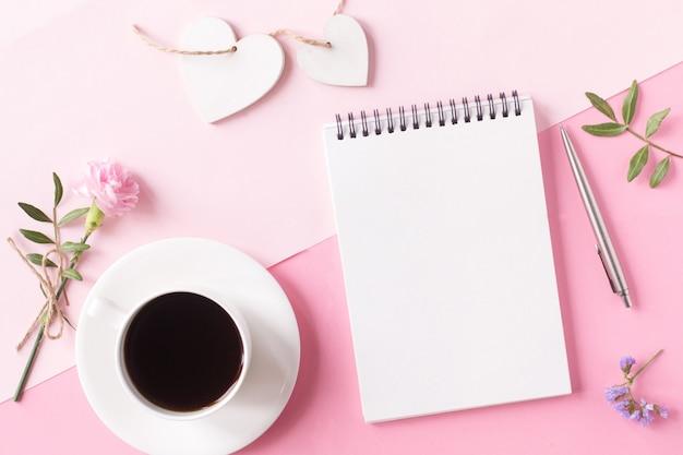Notitieboekje met schone pagina, kopje koffie, bloem, pen en houten hart op roze achtergrond. bovenaanzicht, vlakke stijl.