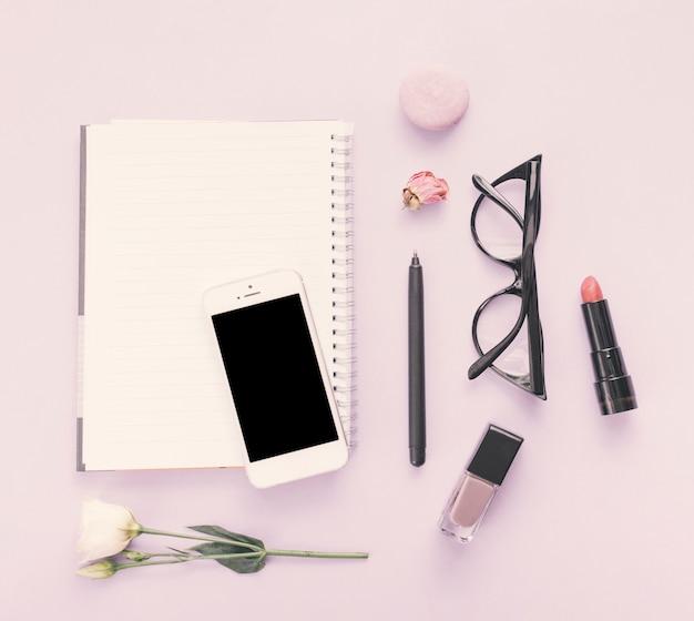 Notitieboekje met smartphone, bloem en schoonheidsmiddelen op lijst