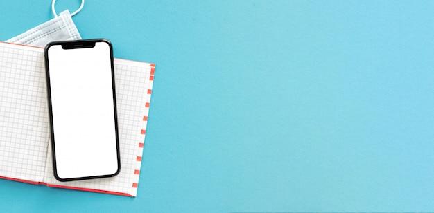 Notitieboekje met smartphone met het lege scherm en medisch gezichtsmasker op blauw achtergrond hoogste concept van het menings het verre werk