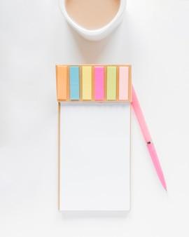 Notitieboekje met stickers dichtbij koffiekop en pen