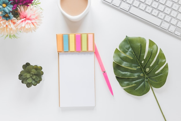Notitieboekje met stickers dichtbij koffiekop, toetsenbord en planten