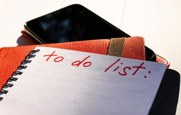 Notitieboekje met takenlijst met telefoon en rood dagboek op een witte houten achtergrond. ruimte kopiëren.