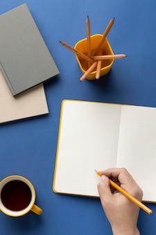 Notitieboekje met takenlijst op bureau met kopje koffie ernaast