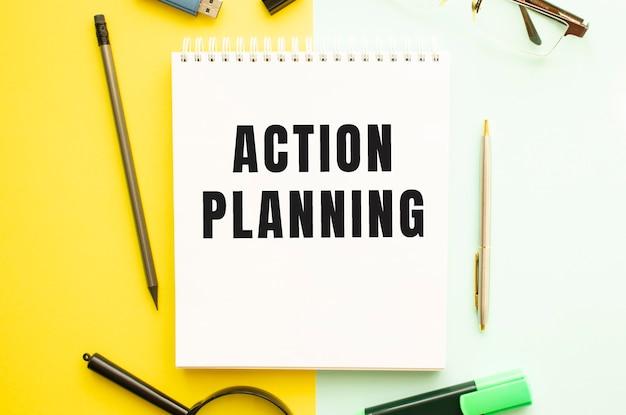 Notitieboekje met tekst actieplanning op kantoortafel met kantoorbenodigdheden. gele kleur achtergrond concept.